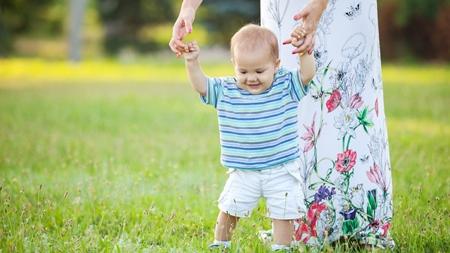赤ちゃんの手を取りながら歩く練習をさせる