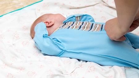 赤ちゃんの服を調節する